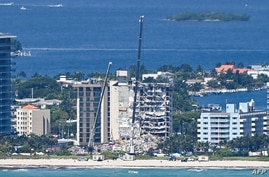 Cranes are seen at a partially collapsed building in Surfside, Florida, north of Miami Beach, on June 27, 2021. - The scores of…