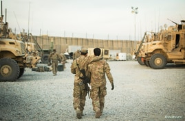 A U.S. soldier from the 3rd Cavalry Regiment walks with the unit's Afghan interpreter before a mission near forward operating…