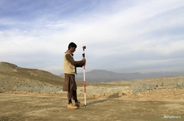A man works at a road construction site, which is being built by a Chinese company, in Khogyani district of Nangarhar province…