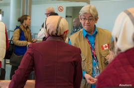 Sharon Chomyn, director of operations for Immigration, Refugees and Citizenship Canada, speaks with Syrian refugees waiting to…