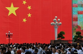 People walk in front of a giant Chinese flag at a central business district ahead of the 70th founding anniversary of People's…
