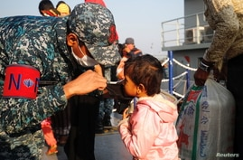 A Bangladesh navy personnel helps a child to wear a mask due to ongoing coronavirus disease (COVID-19).