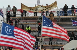 """Supporters of U.S. President Donald Trump hold a """"We the People"""" banner, a Three Percenters flag and a 13-star Betsy Ross U.S…"""
