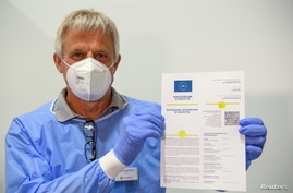 Doctor Christoph Borch shows the new digital COVID-19 vaccination passport COVPASS in Potsdam, Germany, May 27, 2021.