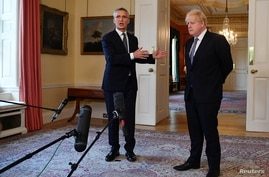 NATO Secretary-General Jens Stoltenberg gestures as he speaks next to Britain's Prime Minister Boris Johnson during a news…