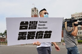 A lawmaker from Taiwan's main opposition Kuomintang (KMT) Party holds signs calling for the government to accept all vaccines.