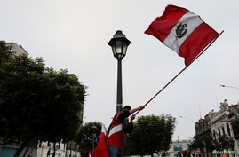 A supporter of Peru's presidential candidate Pedro Castillo waves a Peruvian flag the day after a run-off election, in Lima,…