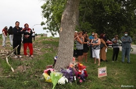 People stand at a makeshift memorial at the fatal crime scene where a man driving a pickup truck jumped the curb and ran over a…