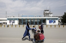 FILE PHOTO: Afghan passengers walk in front of Hamid Karzai International Airport in Kabul, Afghanistan March 29, 2016. …