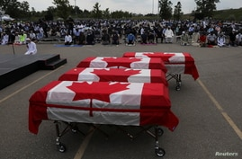 Flag-wrapped coffins are seen outside the Islamic Centre of Southwest Ontario, during a funeral of the Afzaal family that was…