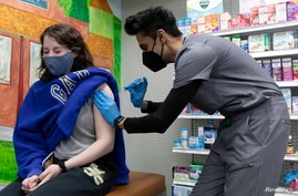 FILE - Julia Gadsby, 18, who has Lupus, receives the Pfizer-BioNTech vaccine against the coronavirus disease (COVID-19) at Skippack Pharmacy in Schwenksville, Pennsylvania, U.S., March 3, 2021.
