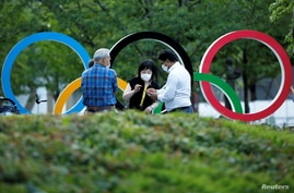 People chat next to Olympic Rings monument outside the Japan Olympic Committee (JOC) headquarters near the National Stadium,…