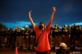 A protestor gestures as police stand guard near the Government House during a demonstration