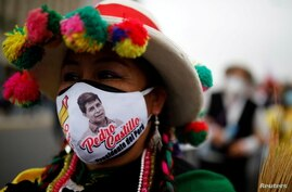 A supporter wearing a face mask with the image of Peru's presidential candidate Pedro Castillo marches in Lima,…