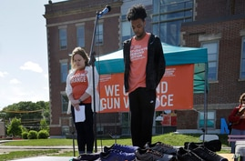 FILE - Kait Saier, left, and Kamren Baxter, right, observe a moment of silence while standing near shoes arranged in the shape of a peace sign to honor shooting homicide victims during a rally against gun violence, June 3, 2018, in Boston.