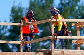 Construction workers talk at a USA Properties Fund site, Tuesday, Feb. 2, 2021, in Simi Valley, Calif.  Hiring has weakened for…
