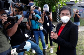Rappler CEO and Executive Editor Maria Ressa, right, wearing a face mask to prevent the spread of the coronavirus, stands in…