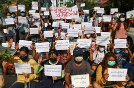 Protesters hold slogans condemning the military government as they mark the Thingyan festival on April 13, 2021 in Yangon, Myanmar.