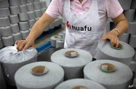 A worker packages spools of cotton yarn at a Huafu Fashion plant, as seen during a government organized trip for foreign…