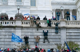 FILE - Violent insurrectionists loyal to President Donald Trump  scale the west wall of the US Capitol, Jan. 6, 2021.