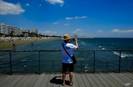 A tourist takes photos the view from the sea in southeeast cost city of Larnaca in the eastern Mediterranean island of Cyprus,…