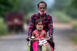 An Indian villager and a child wearing masks on their chin ride on a bicycle on the outskirts of Gauhati, India, Monday, June 7…