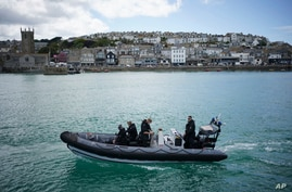 FILE - police officers patrol the harbour in St. Ives, Cornwall, England ahead of the G7 summit that takes place in nearby Carbis Bay.