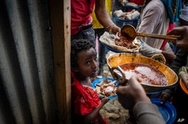 Elena, 7, center, lines up with other displaced Tigrayans to receive food donated by local residents at a reception center for the internally displaced in Mekele, in the Tigray region of northern Ethiopia, May 9, 2021.