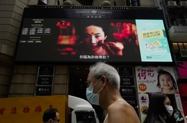 """FILE-People walk past a huge TV screen showing movie listings """"along a downtown street in Hong Kong, Sept. 17, 2020."""