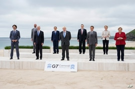 Leaders of the G7 pose for a group photo on overlooking the beach at the Carbis Bay Hotel in Carbis Bay, St. Ives, Cornwall.