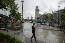FILE - In this Thursday, July 10, 2021 file photo, a woman wearing a face walks in a street in Moscow, Russia. Moscow's mayor…