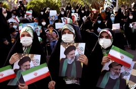 Supporters of presidential candidate Ebrahim Raisi hold signs during a rally in Tehran, Iran, June 16, 2021.