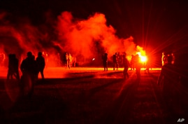 Youths stand in a field during clashes as police tried to break up an unauthorized rave party near Redon, Brittany, Friday June…