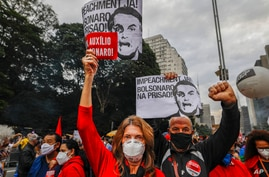 """Demonstrators hold signs that read in Portuguese; """"Impeachment now! Bolsonaro in prison"""" during a protest against Brazilian…"""