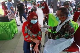 A woman receives a shot of the Sinovac vaccine for COVID-19 during a mass vaccination held by Indonesia military in Medan