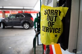 """FILE - An """"Out of Service"""" bag covers a gas pump as cars line up at a Circle K gas station near uptown Charlotte, North Carolina, May 11, 2021, following a ransomware attack that shut down the Colonial Pipeline, a major East Coast gasoline provider."""