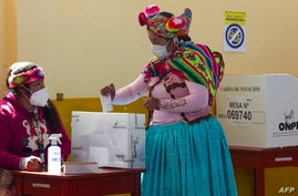 A women wearing traditional quechua attire casts her vote at a polling station in the rural Andean community of Capachica, Peru, June 6, 2021.