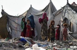 FILE - Children of Afghan refugees play outside tents in Afghan Basti area on the outskirts of Lahore, Pakistan, June 19, 2021.