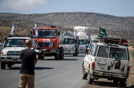 A convoy of trucks from Medecins Sans Frontieres (Doctors Without Borders) carrying medical supplies stops by the side of the…