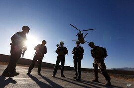 FILE - In this Nov. 30, 2017, file photo, American soldiers wait on the tarmac in Logar province, Afghanistan. With American…