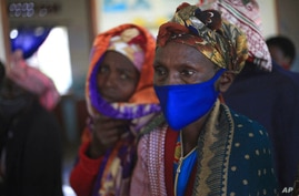 FILE - In this Tuesday, April 27, 2021 file photo, a woman waits for the AstraZeneca coronavirus vaccine at the Butanda Health…