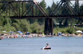 People gather at the Sandy River Delta, in Ore., to cool off during the start of what should be a record-setting heat wave on June 25, 2021.
