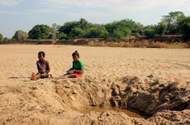 FILE - In this Nov. 11, 2020, file photo, children sit by a dug out water hole in a dry river bed in the remote village of…