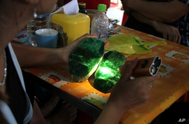 FILE - Local people examine the quality of a jade stone in the Hpakant area of Kachin state, Myanmar.