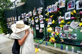 People embrace at a make-shift memorial outside St. Joseph Catholic Church, in Surfside, Fla., Monday, June 28, 2021, near the…