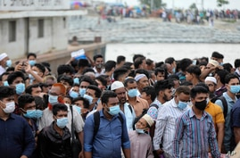 People crowd a ferry terminal to leave the city ahead of a lockdown set to start on July 1, at the Shimulia ferry terminal in Munshiganj, on the outskirts of Dhaka, Bangladesh, June 30, 2021.