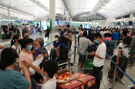 People queue up to check in as some of them are moving to the U.K. at the Hong Kong airport Wednesday, June 30, 2021. Since…