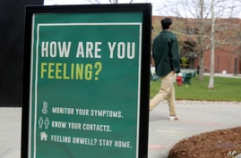 FILE - A sign at the University of Vermont reminds students to monitor their symptoms during the coronavirus pandemic, in Burlington, Vermont, April 27, 2021.