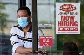 """FILE - A """"Now Hiring"""" sign is seen as a customer leaves a restaurant in Mayfield Heights, Ohio, June 4, 2021. Hiring in the U.S. has picked up with many companies struggling to find enough workers to keep up with the economy's swift recovery."""