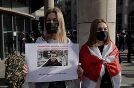 FILE - A woman holds a sign during a protest in Warsaw, Poland, May 24, 2021, against the detention of Belarusian blogger Raman Pratasevich, who was arrested after a passenger plane that he was on was diverted and forced to land Minsk, Belarus.